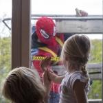 Glazenwassers verkleed als superhelden wassen ramen